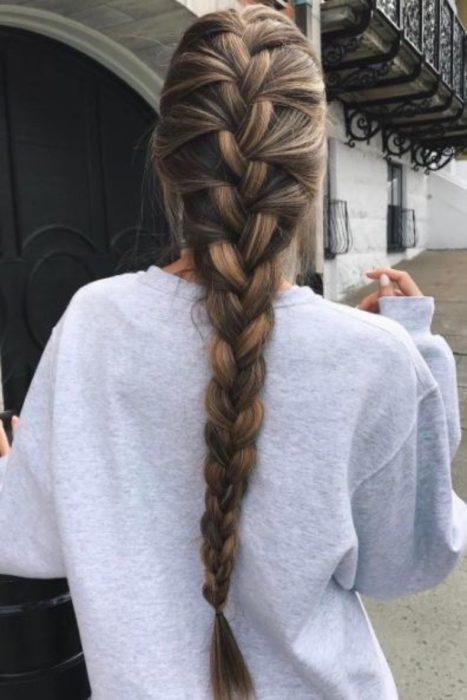 Chica usando sudadera gris peinada con un recogido en trenza completa de cabello largo