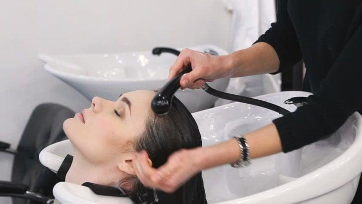 Chica en salón de belleza en dónde le están lavando el cabello, se ve relajada