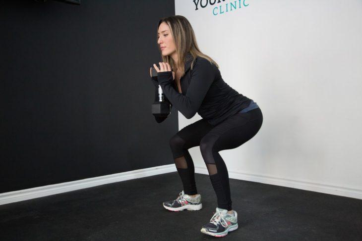 Chica haciendo sentadilla sumo, vestida con ropa deportiva oscura en gimnasio
