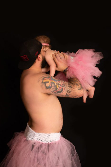 Hombre usando tutu cargando a su hija en brazos