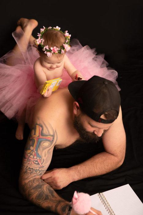 Padre e hija con tutu recostados en n el suelo coloreando un libro