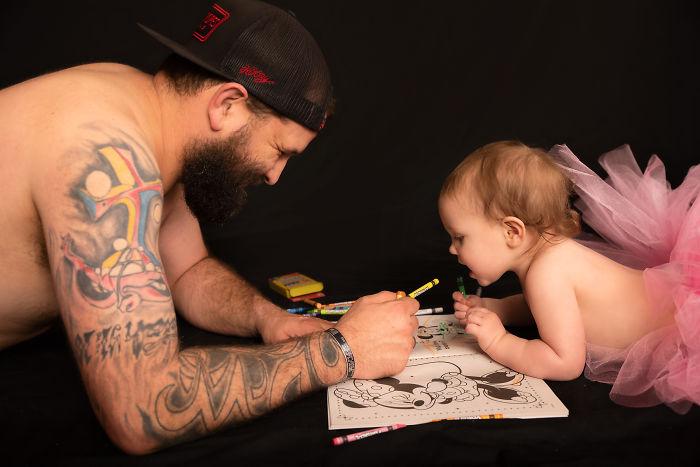 Padre e hija recostados en el suelo coloreando un libro de arte