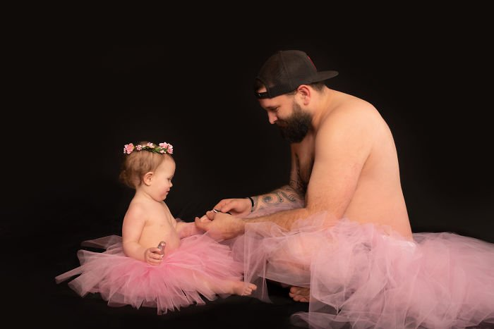 Padre e hija usando tutu sentados en el piso pintándose las uñas