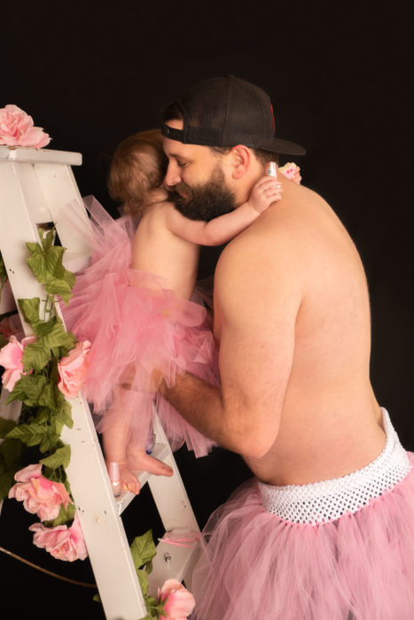 Padre e hija usando tutus, abrazados sobre una escalera