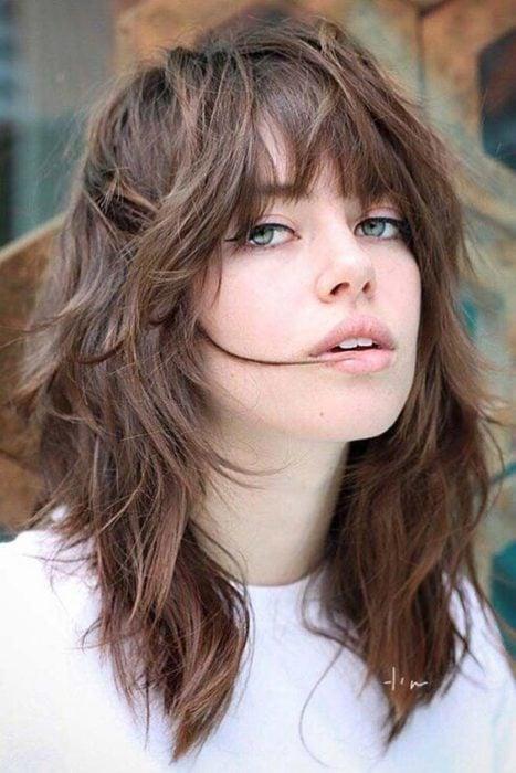 Chica con cabello castaño claro a capas estilo shag, posando para una fotografía