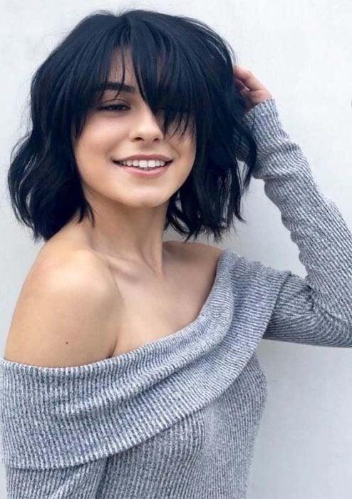 Chica sonriendo, llevando suetér gris claro, mostrando su corte shag y sonriendo