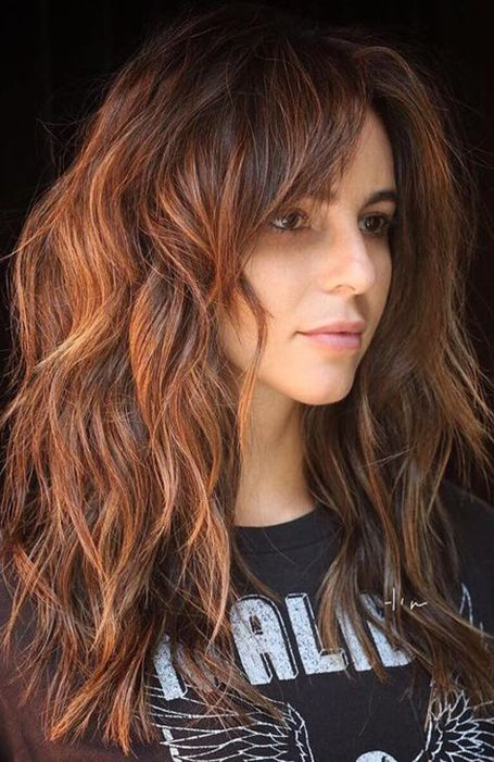 Chica con cabello rojizo cortado en shag posando de perfil