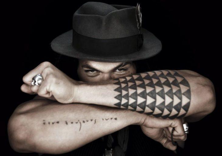 Jason Momoa mostrando los tatuajes que lleve en los antebrazos