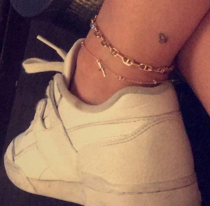 Kylie Jenner mostrando su tobillo con un tatuaje de mariposa