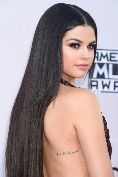 Selena Gomez mostrando su tatuaje en la espalda