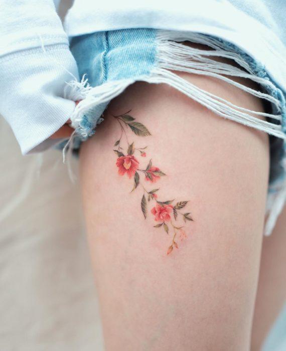 Tatuaje flores tonos cálidos en muslo