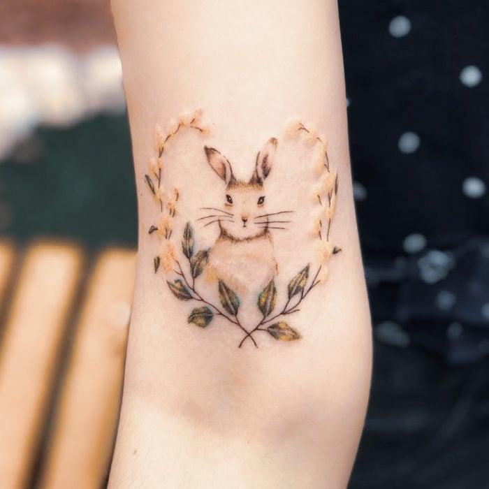 Tatuaje conejo en tonos pastel con flores formando corazón