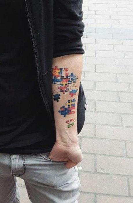 Tatuaje en antebrazo con diseño de rompecabezas de banderas de diferentes países