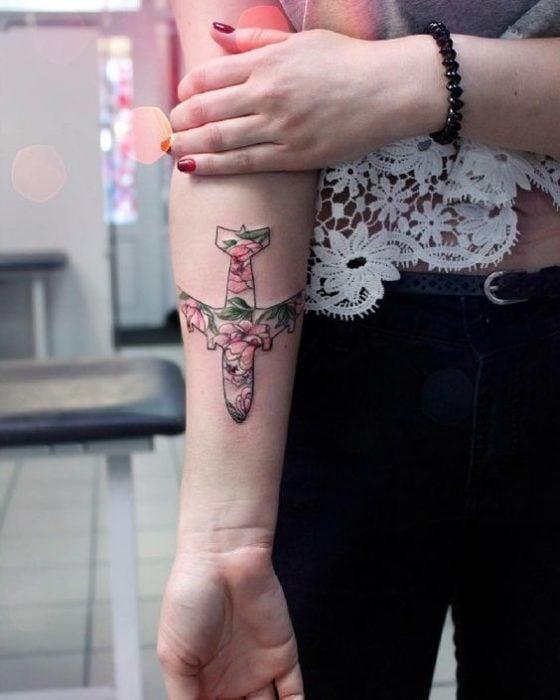 Tatuaje en el antebrazo con diseño de avión con flores de colores