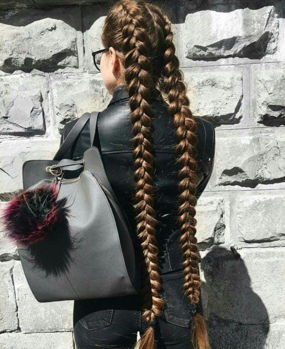 Chica de chamarra de piel negra, con mochila gris, peinada con trenzas holandesas de cabello largo