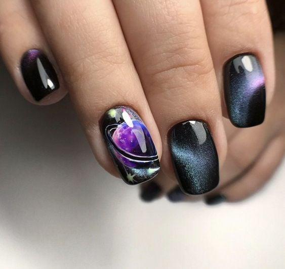 Uñas en negro con sticker de saturno efecto galaxia