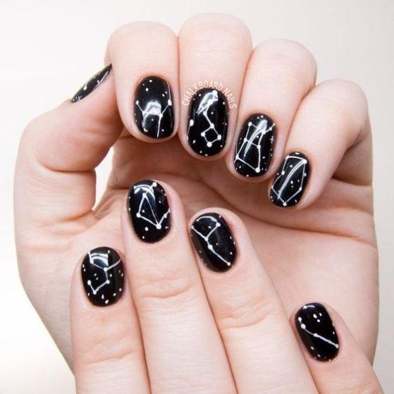 Uñas en negro con diseño de galaxias