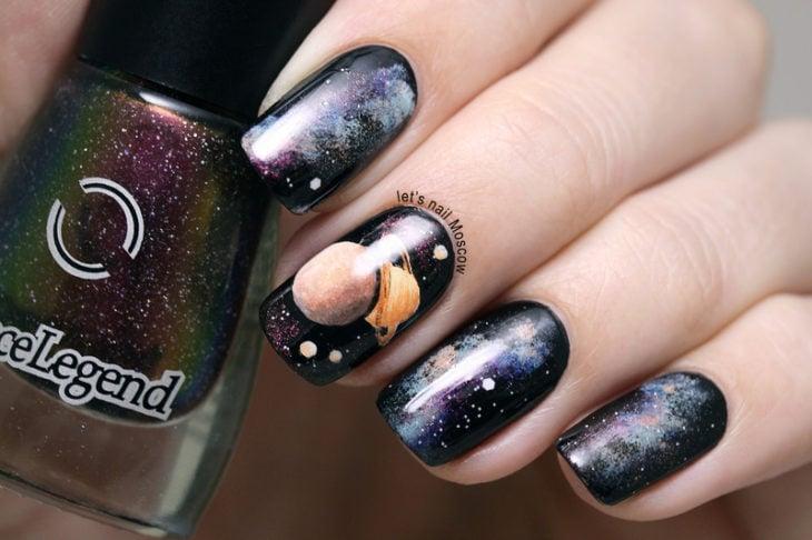 Uñas en negro con diseños de planetas en colores