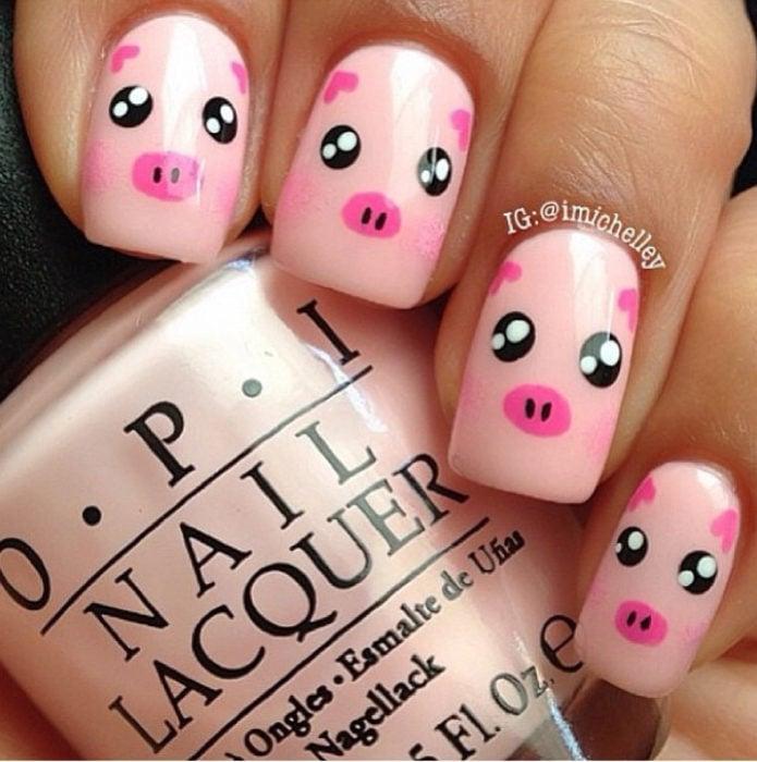 Chica con las uñas pintadas de color rosa y decoradas con un cochinito