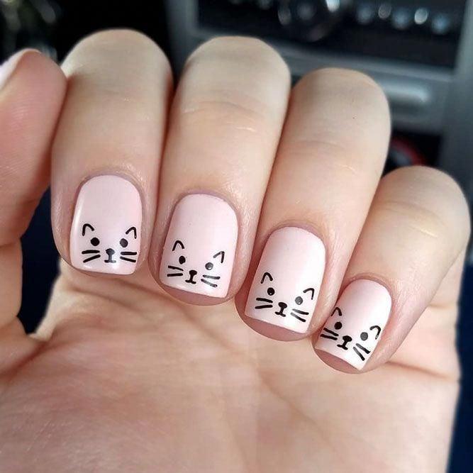 Chica con las uñas pintadas de color rosa y decoradas con un gato