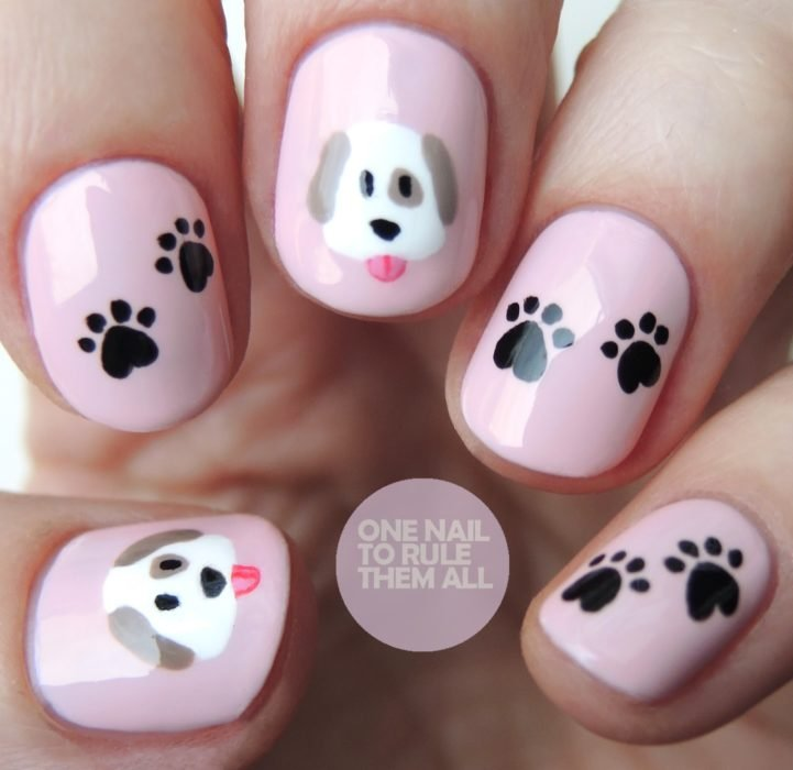 Uñas de color rosa decoradas con un perrito y huellas en color negro
