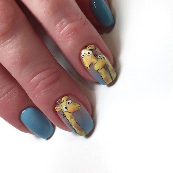 Uñas pintadas de color gris con una jirafa