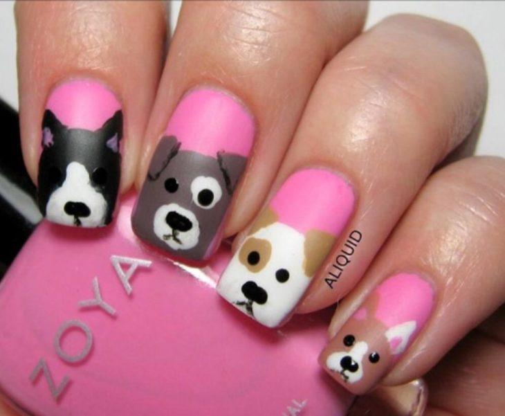 Chica con un las uñas de las manos pintadas de color rosa y con perritos