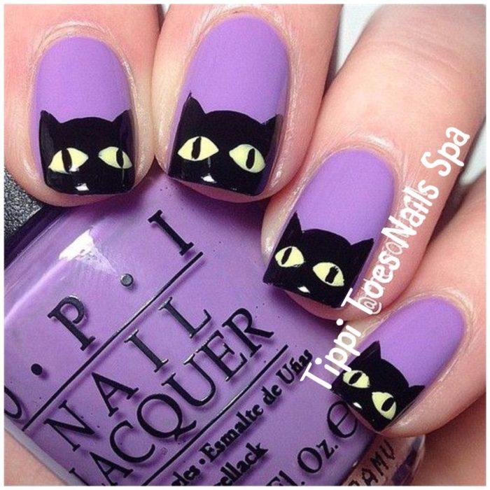 Chica con las uñas de las manos pintadas de color morado y un gato