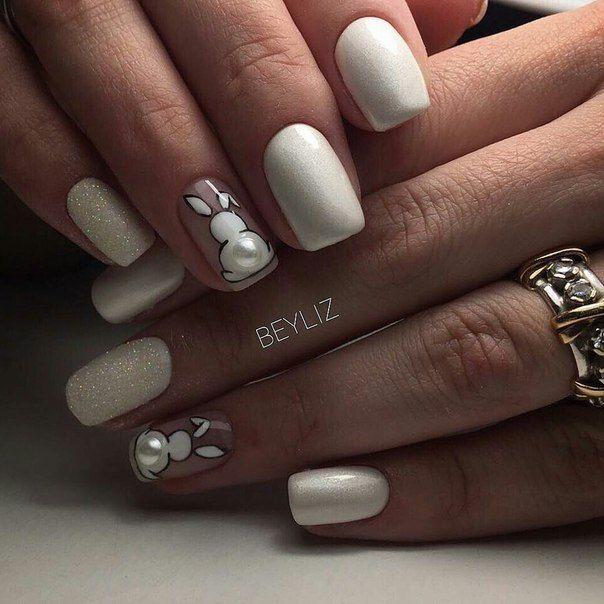 Chica con las uñas de las manos pintadas de color blanco con un conejito