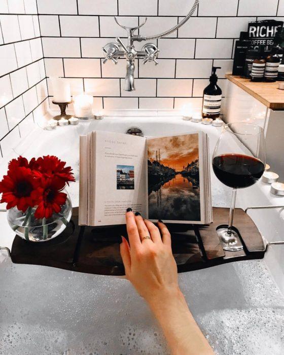 Mujer en la tina disfrutando de un buen vino y leyendo