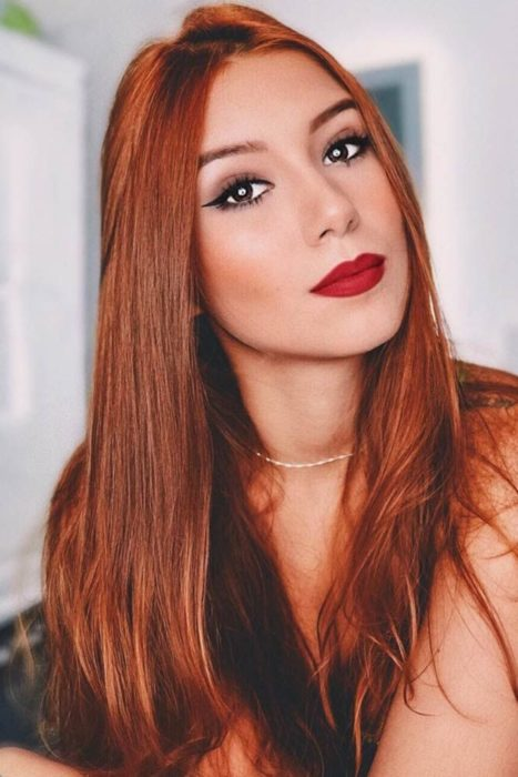 Chica con el cabello de color cobrizo y reflejos en color naranja