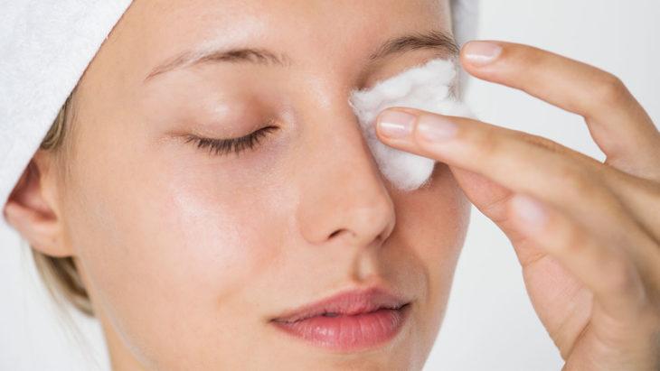 Mujer desmaquillandose los ojos con algodón