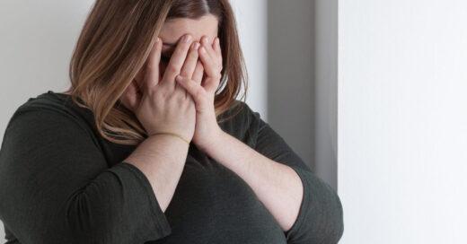 mujer con sobrepeso cubriéndose el rostro