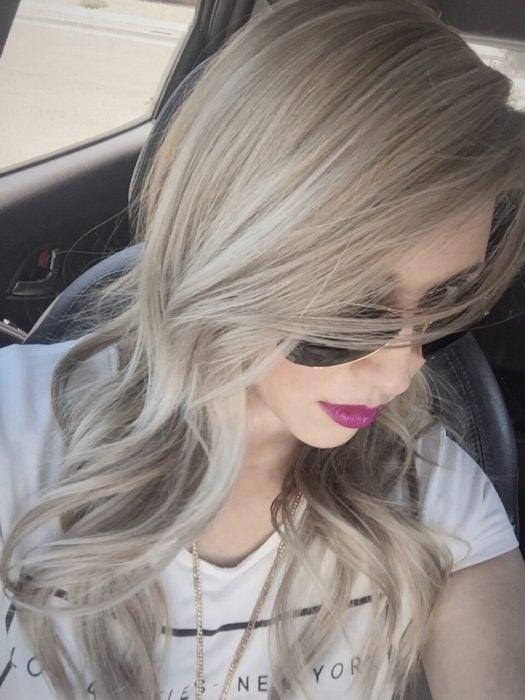 Garota com cabelos tingidos em loira de cinzas douradas