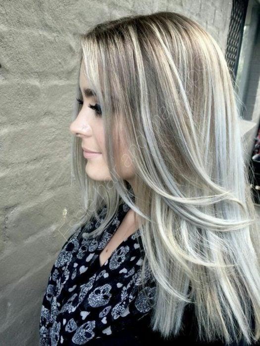 Garota com cabelos tingidos na cor loiro cinza com mechas platinadas