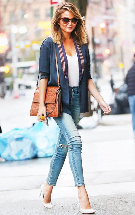 Chica usando un jean skinny, stilettos amarillos y blazer de color azul
