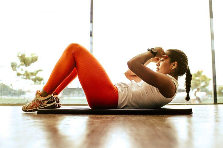 Mujer haciendo abdominales con ropa deportiva