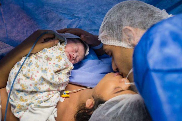 Papás de la bebé que nació enojada, sosteniendo a la pequeña en brazos