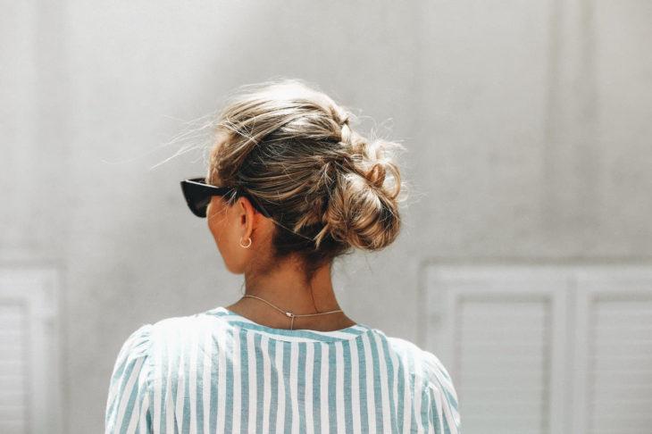 Chica con un moño bajo usando gafas de sol