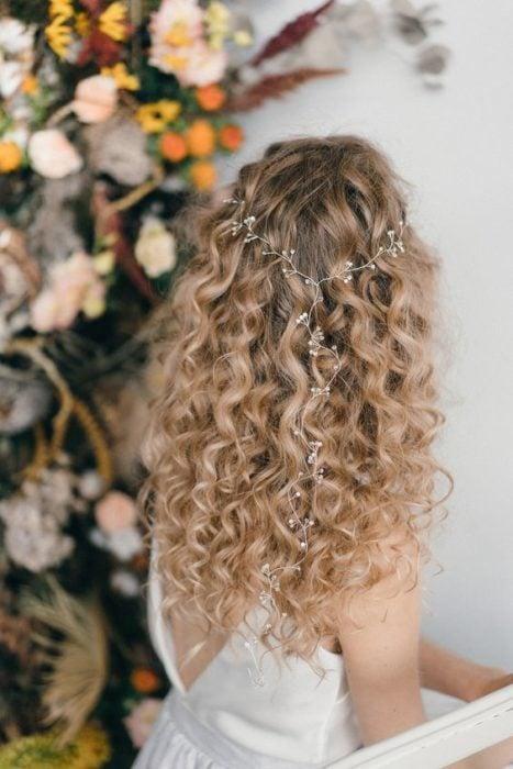 Novia con cabello rizado suelto y un tocado fino