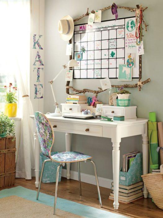 Escritorio blanco, con silla floral y calendario de pizarrón y tonos azules