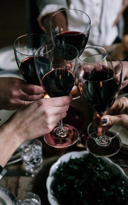 Grupo de chicas brindando con copas de vino tinto