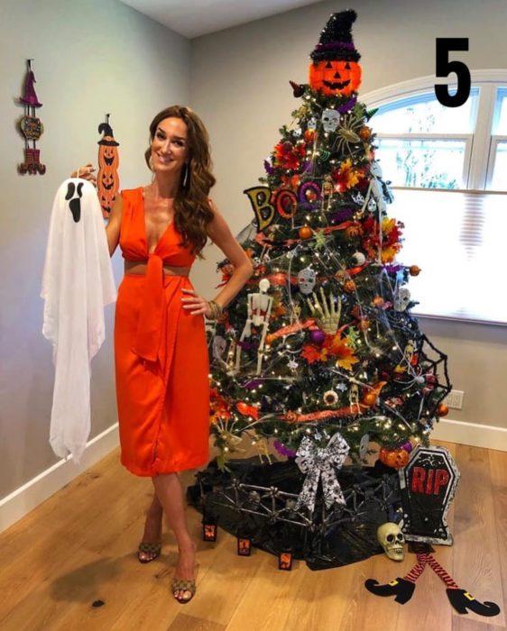 Nadia Colucci, chica junto a un árbol navideño decorado con motivo de Halloween