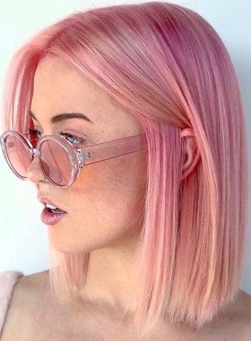 Chica con el cabello pintado de rosa pastel usando gafas de sol