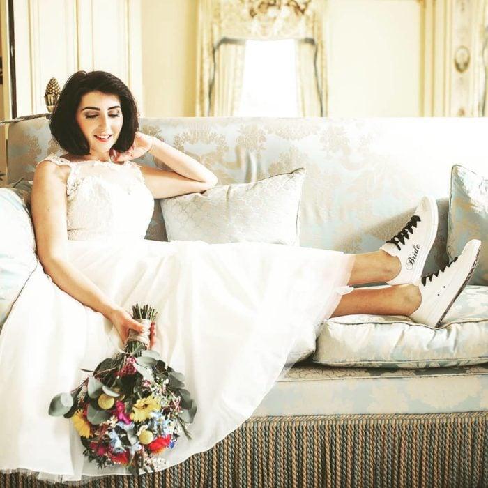 Novia recostada en el sofá llevando vestido blanco y tenis tipo converse