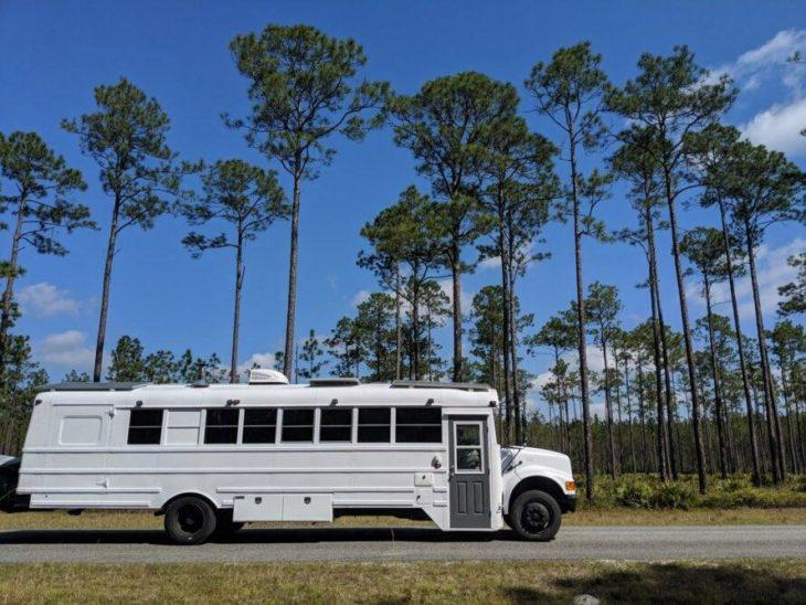 Autobús escolar en color blano viajando por la carretera