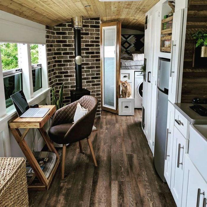 Interior de autobús escolar con pis de madera y cocina integrada