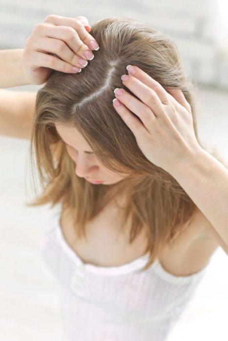 Mujer de cabello castaño mostrando la raíz de su cabello