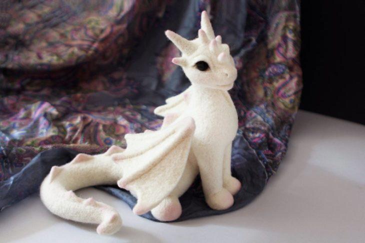 Dragón blanco con pequeños detalles rosados hecho con fieltro
