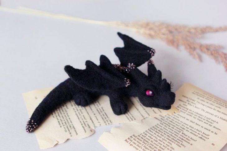 Dragón negro con piedrecillas rosadas y ojos morados hecho a mano